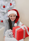 Happy smiling woman give a present for you near Christmas tree Stock Photo