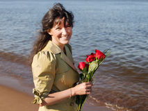 Happy smiling woman in green coat with roses bouquet squinting a royalty free stock images