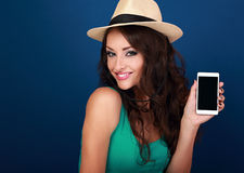 Happy smiling woman in hat holding in hand and showing modern mo Stock Photos