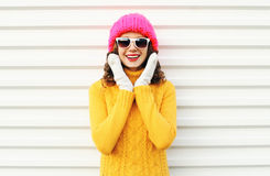 Happy smiling woman having fun wearing colorful knitted pink hat over white Stock Photo