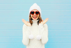 Happy smiling woman having fun wearing a heart shape sunglasses, knitted hat, sweater over blue Stock Image