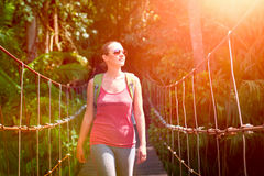 Happy smiling woman hiker crossing suspension bridge in sunlight Royalty Free Stock Photos