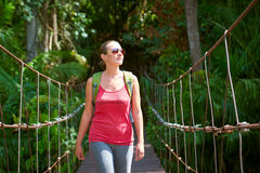 Happy smiling woman hiker crossing suspension bridge in sunlight Royalty Free Stock Image