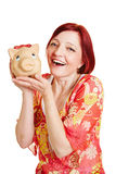 Happy woman holding piggy bank. Happy smiling woman holding a big piggy bank Stock Photos
