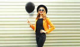 happy smiling woman holding black helium air balloon posing stock photos