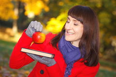 Happy smiling woman holding book and apple in autumn park Royalty Free Stock Images