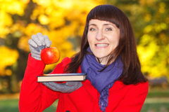 Happy smiling woman holding book and apple in autumn park Stock Images