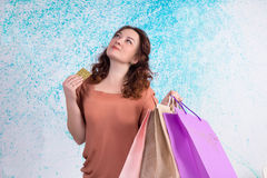 Happy smiling woman holding colorful shopping paper bags, bank c Royalty Free Stock Photos