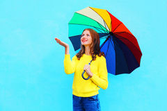 Happy smiling woman holding colorful umbrella in autumn day looking up over colorful blue background Stock Photos