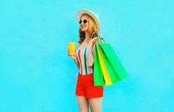 Happy smiling woman holding cup of fruit juice with shopping bags wearing colorful t-shirt, summer straw hat, sunglasses royalty free stock images