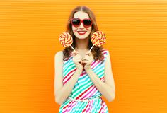 Happy smiling woman holding lollipop in red heart shaped sunglasses, colorful striped dress on orange wall stock photos