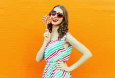 Happy smiling woman holding lollipop in red heart shaped sunglasses, colorful striped dress on orange wall royalty free stock image