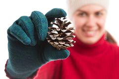 Happy smiling woman holding a pine cone. Wearing hat and gloves as joyful winter holidays concept Royalty Free Stock Images