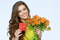 Happy smiling woman holding presents. Flowers and gift box. Stock Images