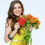 Happy smiling woman holding presents. Flowers and gift box. White background isolated stock image