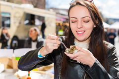 Happy smiling woman holding a single fresh opened oyster. At outdoor food festival Stock Photos