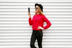Happy smiling woman holding smartphone in colorful pink knitted sweater on city white wall. Background royalty free stock photo
