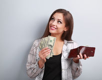 Happy smiling woman holding wallet and dollars and thinking how Stock Photography