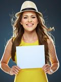 Happy smiling woman holding white blank board. Yellow dress Royalty Free Stock Photo