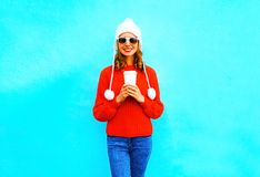 Happy smiling woman holds a coffee cup in red sweater. Hat on a blue background Stock Photography