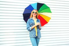 Happy smiling woman holds colorful umbrella posing on white. Background stock images