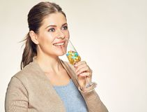 Happy smiling woman holds vine glass with vitamin pills. Isolated studio portrait Stock Images