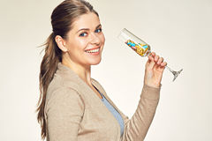 Happy smiling woman holds vine glass with vitamin pills Stock Image