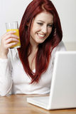 Happy smiling woman at home on laptop Stock Photography
