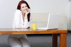 Happy smiling woman at home on laptop Stock Images