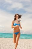 Happy smiling woman jogging on the beach Stock Photo