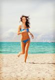 Happy smiling woman jogging on the beach Stock Images