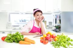 Happy smiling woman in kitchen Royalty Free Stock Image