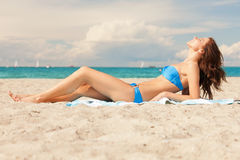 Happy smiling woman laying on a towel. Picture of happy smiling woman laying on a towel Royalty Free Stock Images