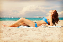 Happy smiling woman laying on a towel Stock Images