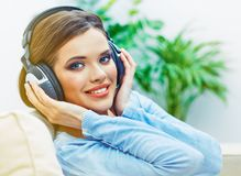 Happy smiling woman listening music with headphones. Smiling girl relax at home Royalty Free Stock Photography