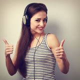 Happy smiling woman listening the music showing thumb up sign. V Royalty Free Stock Image