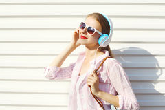 Happy smiling woman listens to music in headphones over white Royalty Free Stock Images