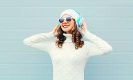 Happy smiling woman listens to music headphones wearing a sunglasses, knitted hat, sweater over blue Stock Photos
