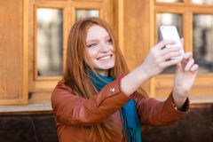 Happy smiling  woman with long red hair making selfie. Happy smiling beautiful young woman with long red hair in leather jacket and scarf making selfie in Royalty Free Stock Photos