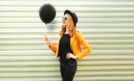 happy smiling woman looking at black helium air balloon in round hat royalty free stock photo
