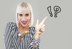 Happy smiling woman looking at written drawings of question mark. S on gray background. Idea Concept stock photo