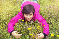A happy smiling  woman is lying in a meadow Stock Photos