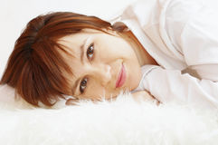 Happy smiling woman lying on white fur plaid Royalty Free Stock Photography