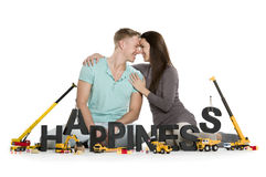 Happy smiling woman and man building happiness-word. Stock Image