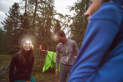 Happy smiling woman and man with headlamp flashlight during evening near camping. Group of friends people summer Stock Images