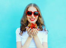 Happy smiling woman with many strawberry over blue Royalty Free Stock Photo