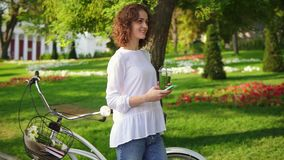 Happy smiling woman messaging using her smartphone standing in the city park near her city bicycle with flowers in its. Basket and drinking green detox smoothie stock video