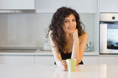 Happy smiling woman in the morning. Portrait of happy smiling woman in the morning resting her chin on hand, having coffee or tea Stock Image