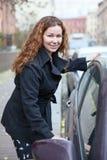 Happy smiling woman opeing car door Stock Photos