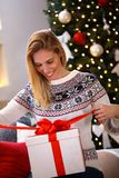 Smiling woman opening Christmas gift Stock Photo